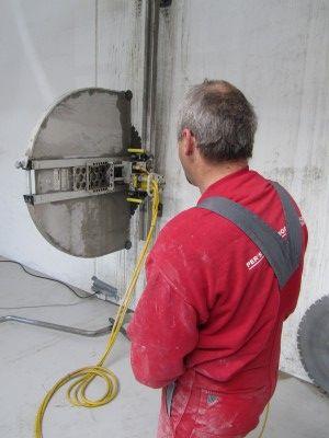 En mand står og observerer diamantskæring af en betonvæg.