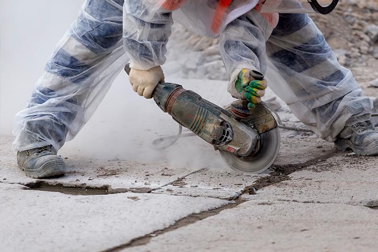 En mand der udfører diamantskæring på et betongulv.