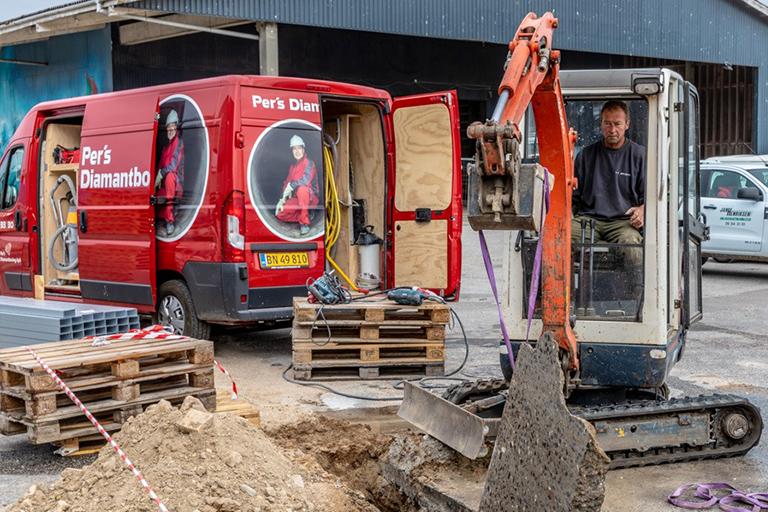 En kranvogn har fat i et stykke beton efter wireskæring.